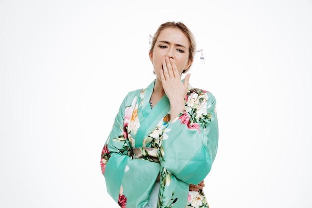 Vrouw in traditionele japanse kimono die er moe en verveeld uitziet terwijl ze de hand op de mond houdt op wit
