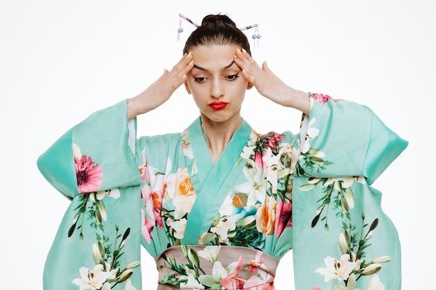 Vrouw in traditionele japanse kimono die er onwel en geïrriteerd uitziet en haar slapen aanraakt met sterke hoofdpijn op wit