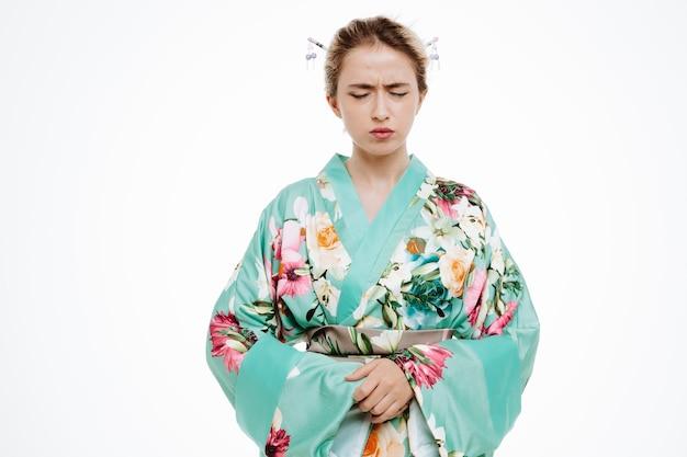 Vrouw in traditionele japanse kimono die er onwel uitziet en haar maag aanraakt die lijdt aan pijn op wit