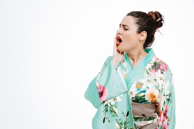 Vrouw in traditionele japanse kimono die er onwel uitziet en haar wang aanraakt, voelt kiespijn op wit