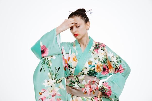 Vrouw in traditionele japanse kimono die er onwel uitziet en hand op haar voorhoofd houdt met sterke hoofdpijn op wit