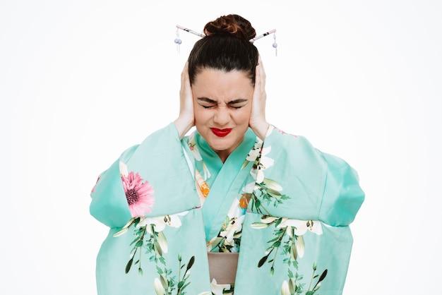 Vrouw in traditionele japanse kimono die geërgerd uitkijkt over het sluiten van tijdperken met handen die last hebben van ruis op wit