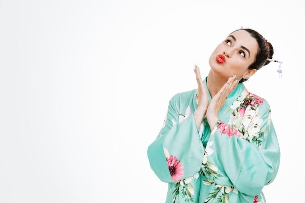 Vrouw in traditionele japanse kimono die gelukkig en positief opkijkt en lippen houdt, zoals gaan kussen terwijl ze elkaars handen vasthoudt op wit