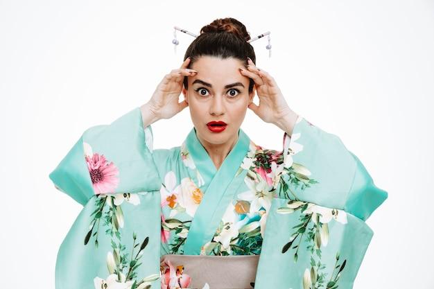 Vrouw in traditionele japanse kimono die geschokt is en handen opsteekt die tempels op wit aanraakt?