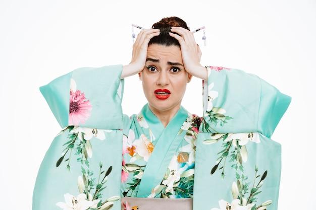Vrouw in traditionele japanse kimono die gestrest en verward is, hand in hand op haar hoofd op wit