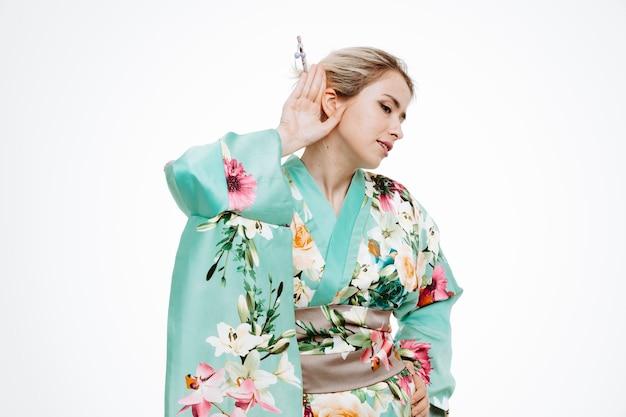 Vrouw in traditionele japanse kimono die hand op oor houdt en naar roddels op wit probeert te luisteren