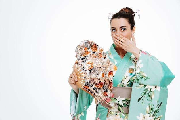 Vrouw in traditionele japanse kimono die handventilator vasthoudt, geschokt door de mond met de hand op wit
