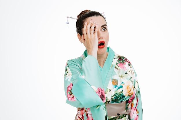 Vrouw in traditionele japanse kimono die opzij kijkt geschokt kegelvormig gezicht met hand op wit