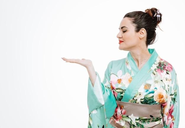 Vrouw in traditionele japanse kimono die opzij kijkt met een glimlach op een blij gezicht en iets presenteert met de arm van haar hand op wit