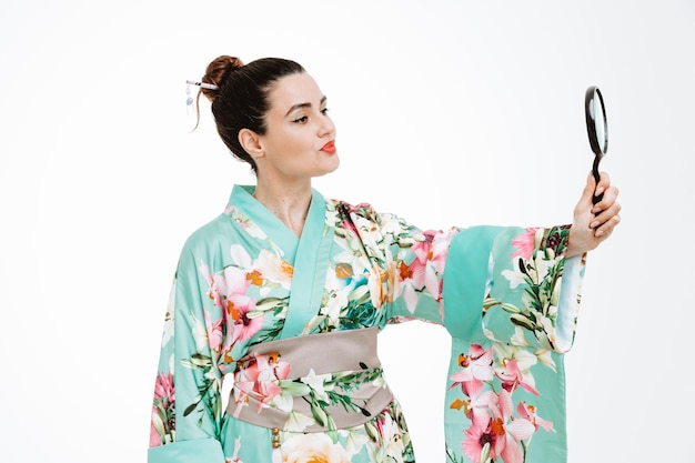 Vrouw in traditionele japanse kimono die vergrootglas vasthoudt en ernaar kijkt met een serieuze zelfverzekerde uitdrukking op wit