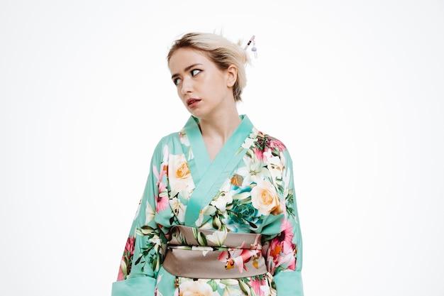 Vrouw in traditionele japanse kimono kijkt opzij en is geïrriteerd en geïrriteerd met rollende ogen op wit