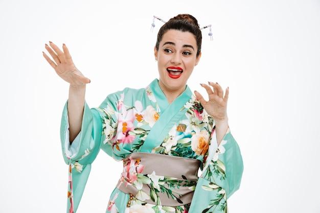 Vrouw in traditionele japanse kimono kijkt verward opzij en maakt verdedigingsgebaar met handen op wit