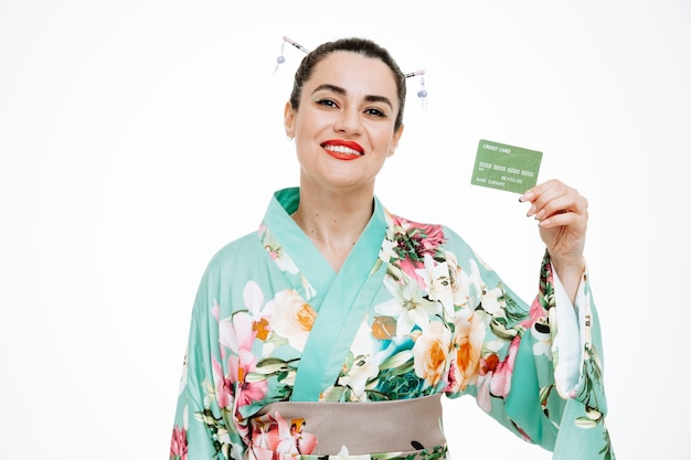 Vrouw in traditionele japanse kimono met creditcard blij en tevreden glimlachend breed op wit