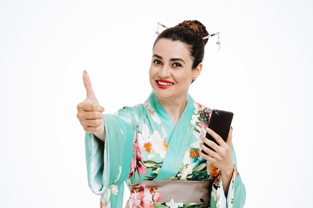 Vrouw in traditionele japanse kimono met smartphone die duim op wit toont
