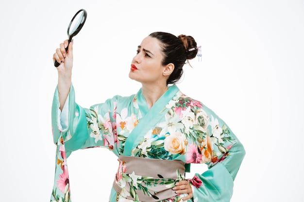 Vrouw in traditionele japanse kimono met vergrootglas kijkend naar het geïntrigeerd op wit