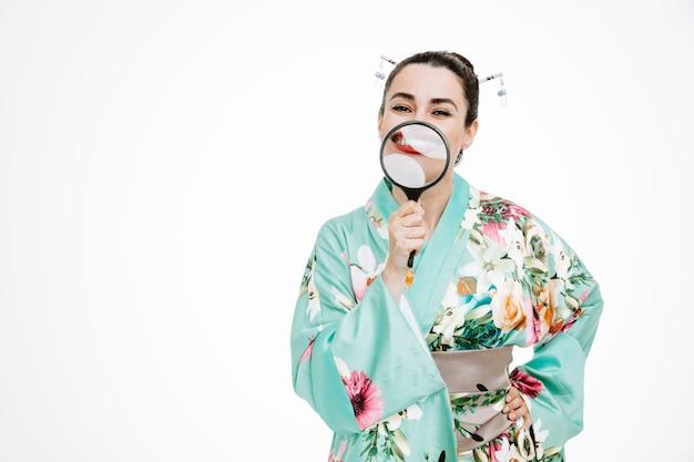Vrouw in traditionele japanse kimono met vergrootglas voor haar gezicht glimlachend breed op wit