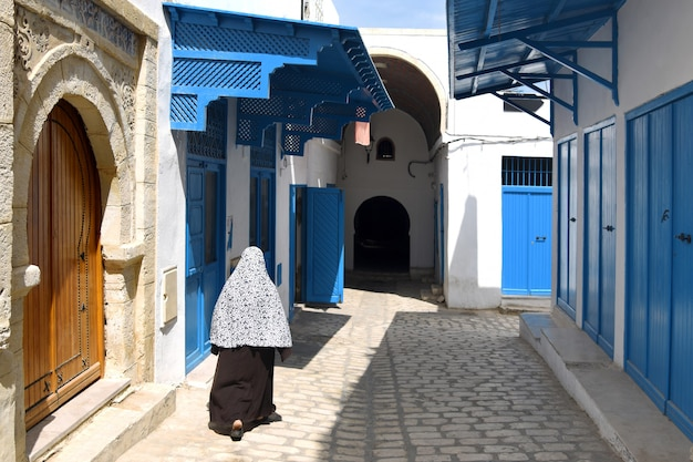 Vrouw in traditionele kleding loopt langs een smal straatje in de oude stad van sousse in tunesië
