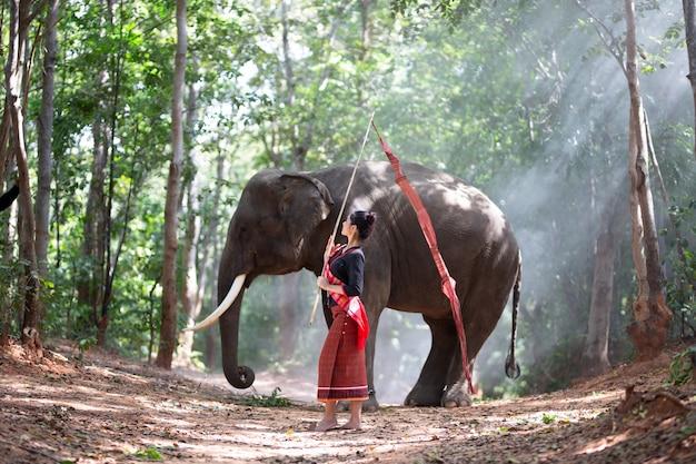 Vrouw in traditionele kostuum en olifantszitting in bos voor reis en levensstijlconcept