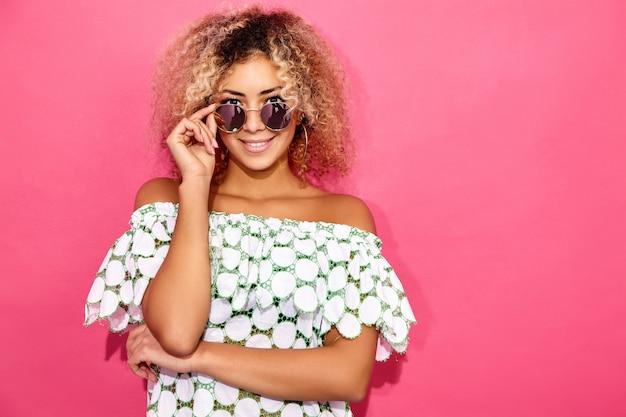 Vrouw in trendy de zomerkleren die en zonnebril stellen opstijgen