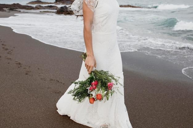 Vrouw in trouwjurk op het strand