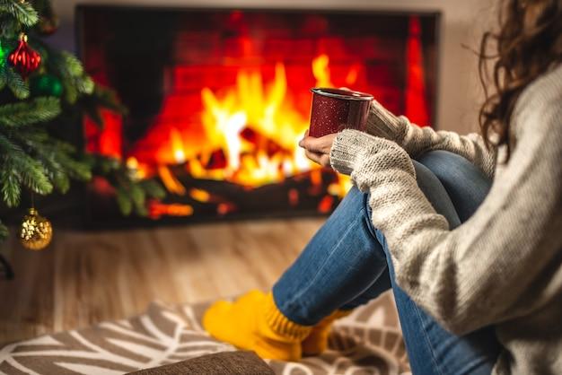 Vrouw in trui en warme sokken zit voor de open haard, die op het tv-scherm is afgebeeld