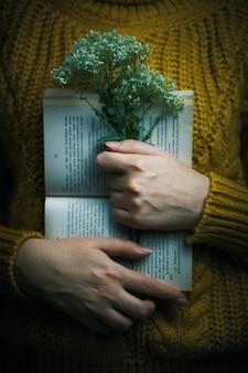 Vrouw in trui houdt boek en boeket open papieren boek en wilde bloemen in armen van warme kn...
