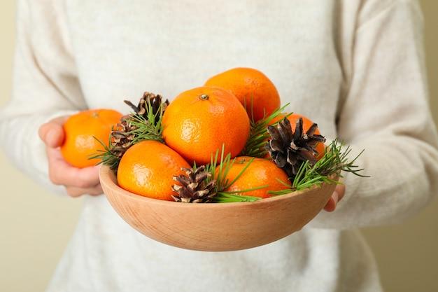 Vrouw in trui houdt kom met mandarijnen vast, close-up