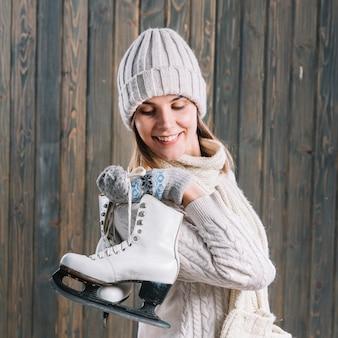 Vrouw in trui met schaatsen achter rug