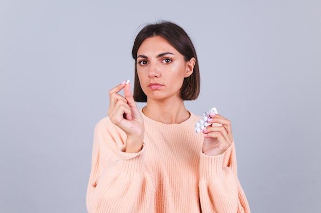 Vrouw in trui op grijze muur houdt mok en pillen vast met een ongelukkige droevige uitdrukking op het gezicht