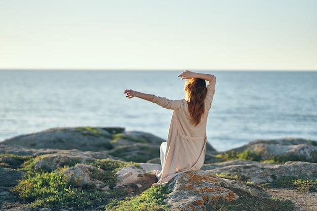 Vrouw in truien met opgeheven handen op een steen in de buurt van de zee in de bergen