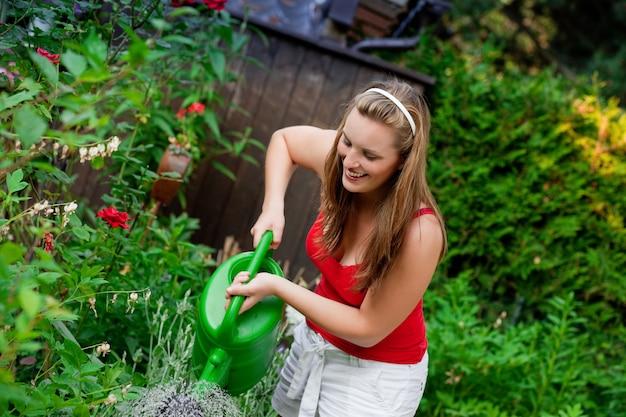 Vrouw in tuin het water geven bloemen