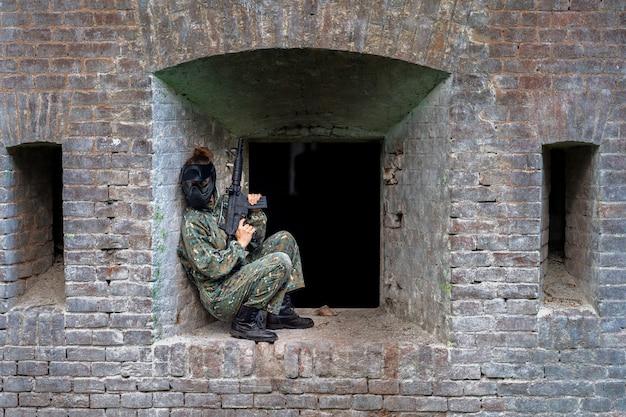 Vrouw in uniform met een pistool in militaire paintballtraining