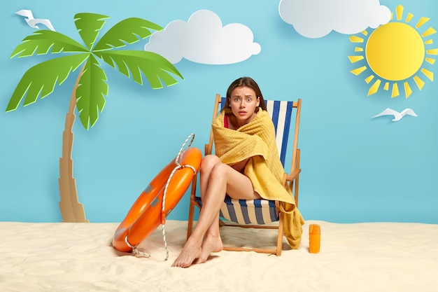 Vrouw in verlegenheid gebracht bedekt met gele handdoek, poseert op ligstoel