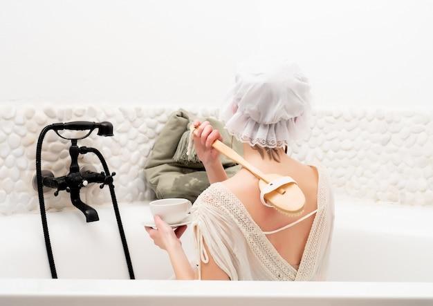 Vrouw in vintage kleding neemt een bad met lavendel en drinkt een kopje koffie
