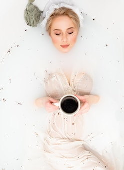 Vrouw in vintage kleding neemt een bad met lavendel zoals in de dagen van de renaissance en drinkt een kopje koffie