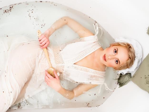 Vrouw in vintage kleding neemt een bad met lavendel zoals in de tijd van de renaissance