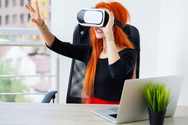 Vrouw in virtual reality headset wijzend in de lucht terwijl op haar werkplek op kantoor.