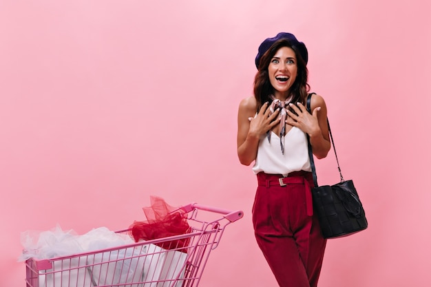 Vrouw in vreugdevolle verrassing kijkt naar de camera en poseert naast roze trolley. dame in witte blouse en lichte broek lacht op geïsoleerde achtergrond.