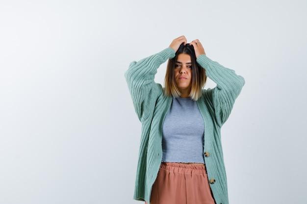 Vrouw in vrijetijdskleding die handen op het hoofd houdt en verontrust, vooraanzicht kijkt.