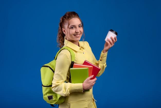 Vrouw in vrijetijdskleding die wegwerp cappuccino-kop houdt en rugzak houdt die op blauwe muur wordt geïsoleerd