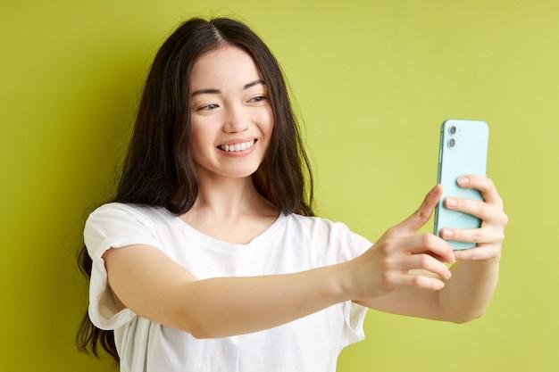 Vrouw in vrijetijdskleding neemt foto op smartphone geïsoleerd op groene achtergrond studio portret. mensen oprechte emoties levensstijl concept. bespreek kopie ruimte. selfie geschoten op mobiele telefoon