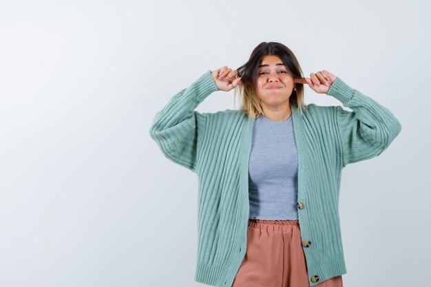Vrouw in vrijetijdskleding oren met vingers inpluggen, wangen blazen en verbaasd, vooraanzicht op zoek.