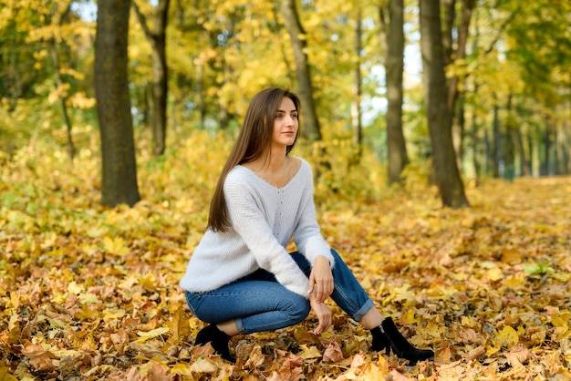 Vrouw in vrijetijdskleding poseren in park met gele bladeren