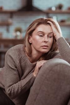 Vrouw in wanhoop. aantrekkelijke rijpe vrouw met donkere ogen die op de bank zit en zich wanhopig voelt