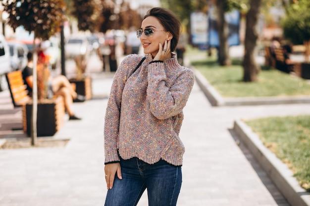Vrouw in warme doeken buiten in de herfstpark