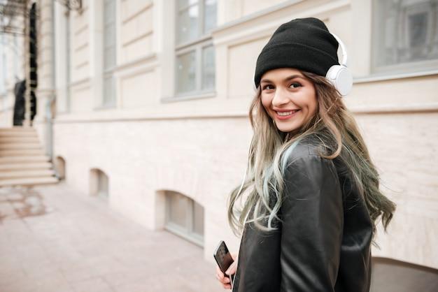 Vrouw in warme kleding en hoofdtelefoon