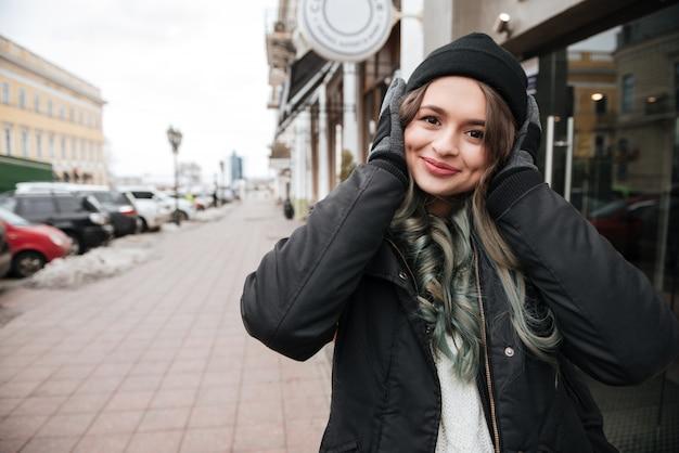 Vrouw in warme kleren luisteren muziek op straat