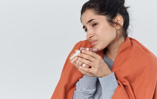 Vrouw in warme kleren met een servet in haar hand loopneus gezondheidsproblemen een kopje thee. hoge kwaliteit foto