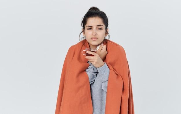 Vrouw in warme kleren met een servet in haar handloopneus