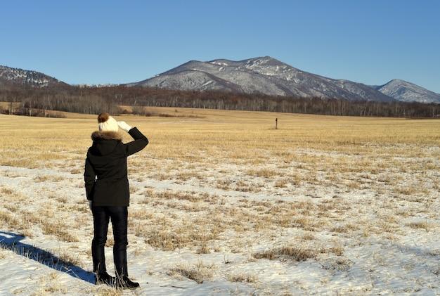 Vrouw in warme kleren staan in het veld en kijken naar besneeuwde bergen